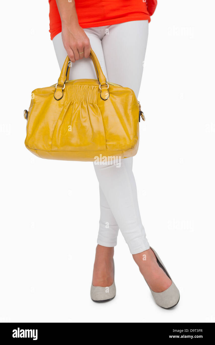Woman in high heels standing with yellow bag - Stock Image