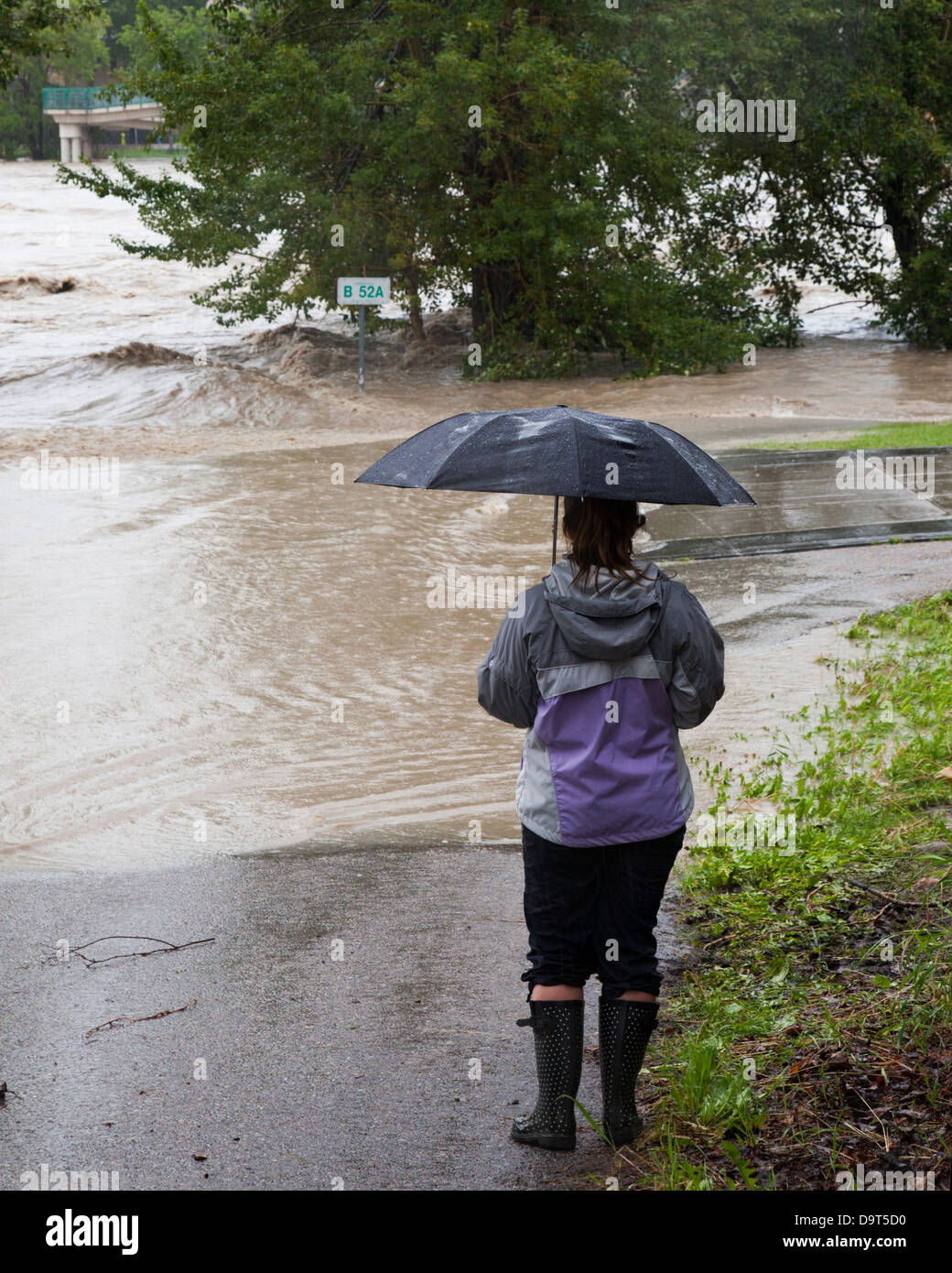 Woman holding umbrella watching the Bow River breach the bank and flood the pedestrian path in downtown Calgary - Stock Image