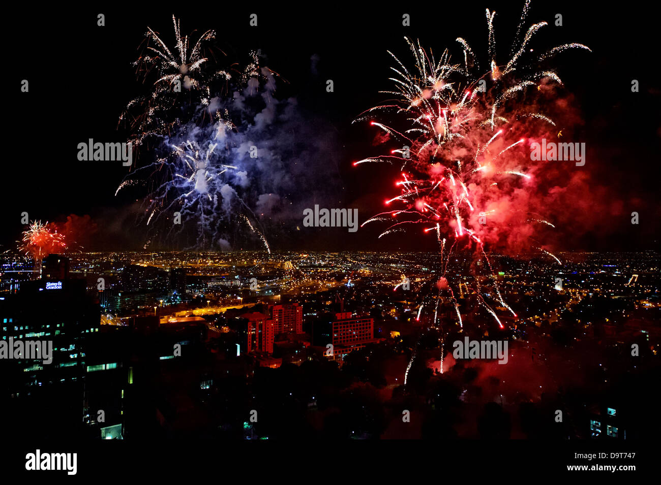 Spectacular fireworks photographed from atop a skyscraper light up the night sky over Melbourne Australia. - Stock Image