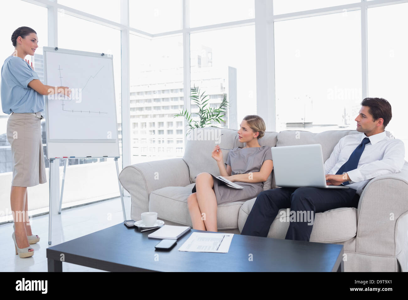 Business woman presenting something on a whiteboard - Stock Image