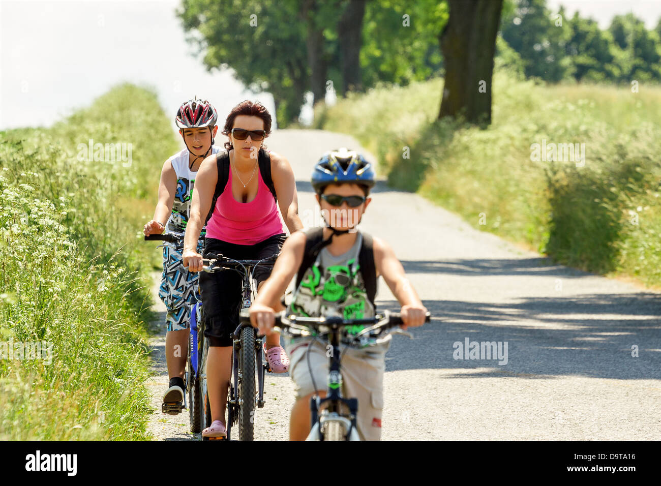 Mother with two sons riding bike on bicycle trip, focus to mother Stock Photo