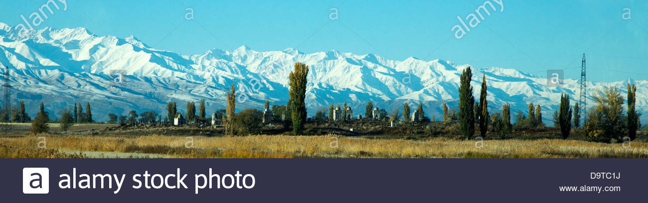 Kyrgyzstan, Moslem cemetery with Tian Shan Mountains - Stock Image
