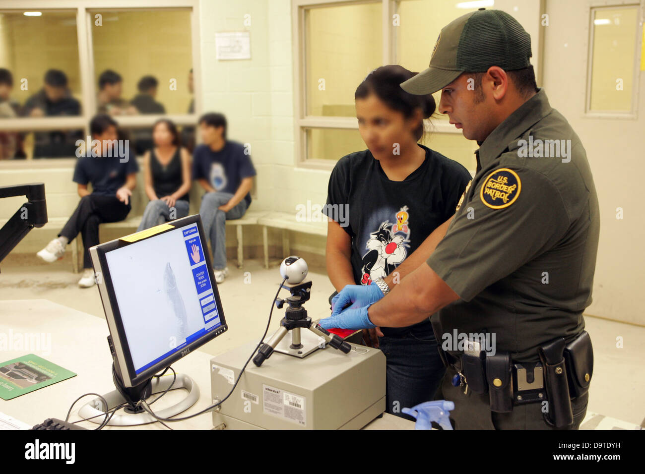 Border Patrol Agent Finger Prints Illegal Alien. - Stock Image