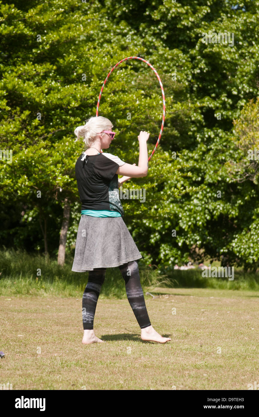 A girl plays with a hula hoop in a park in Britain in the summer - Stock Image