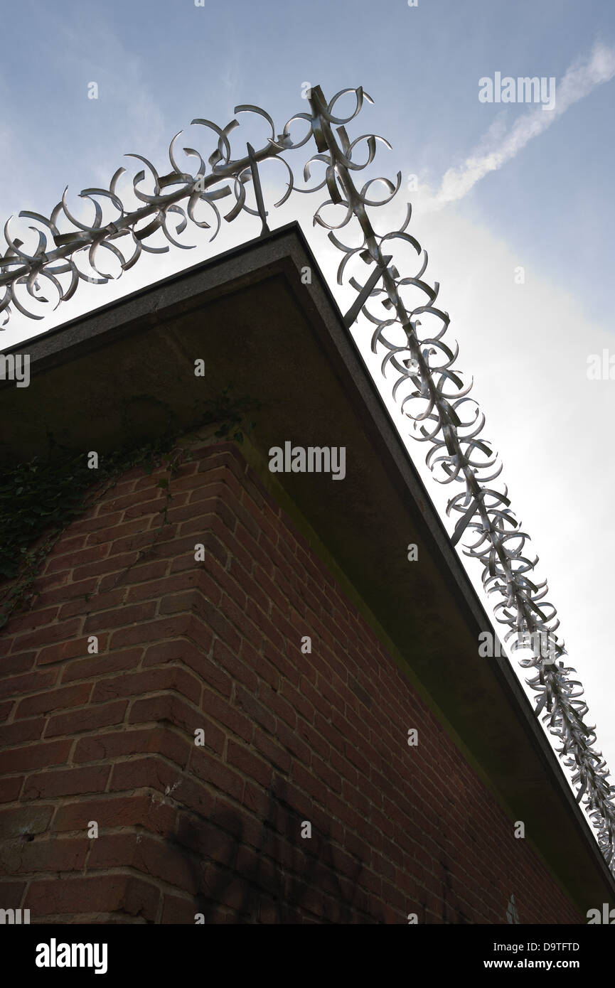 Keep out security fence protecting from burglary against an early morning sky with rotating sharp knife anti climb - Stock Image