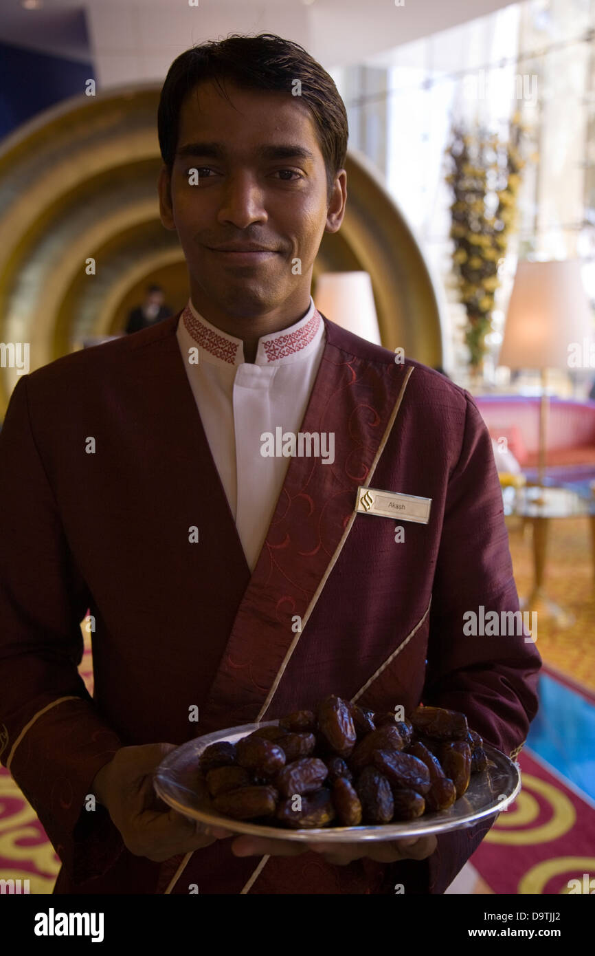 Doormen at the ultra-luxe Burj al-Arab hotel welcome guests with a tray of tasty dates, Dubai, U.A.E. - Stock Image