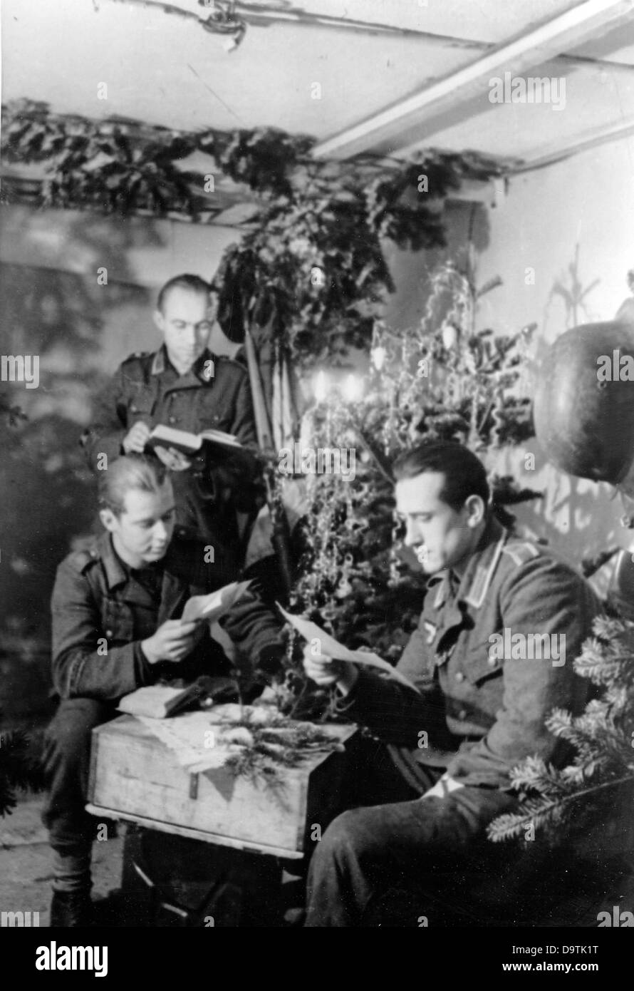 The soldiers of the German Wehrmacht read letters in a bunker on the Eastern Front on Christmas 1944. The Nazi Propaganda! Stock Photo