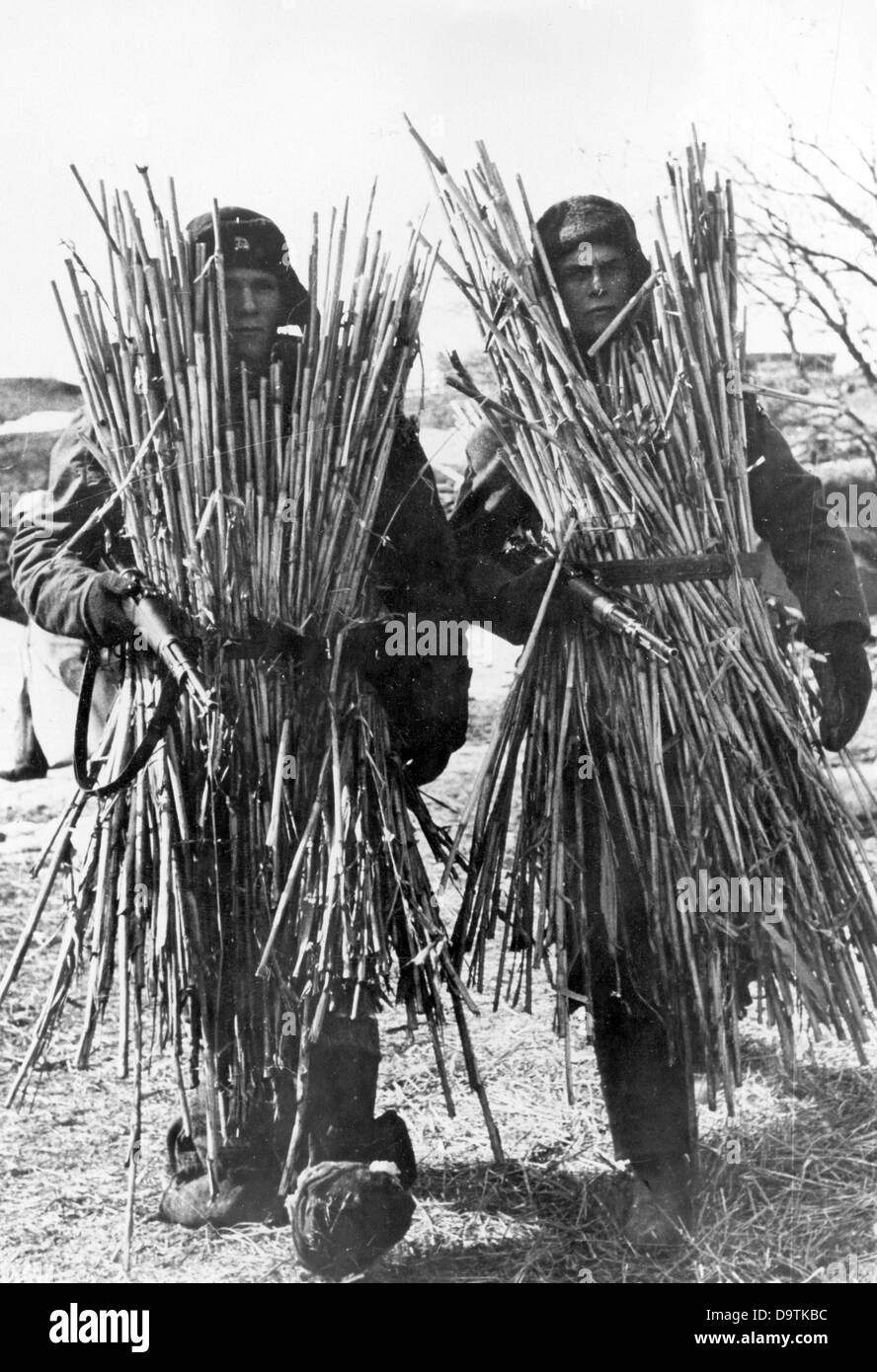 Camouflaged soldiers are pictured at the Eastern Front, date and place unknown. The Nazi Propaganda! on the back - Stock Image
