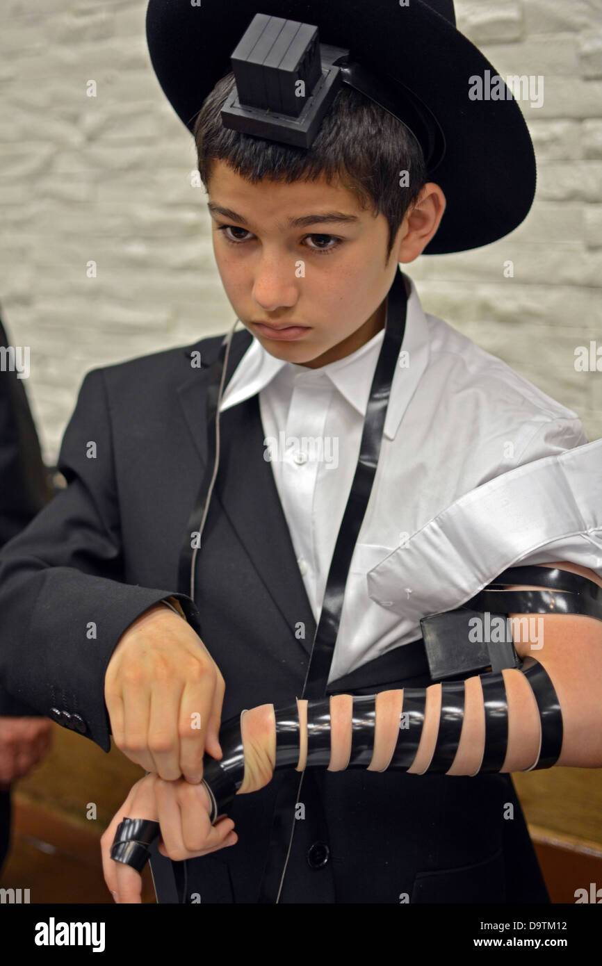 Young religious Jewish boy puts on phylacteries - teffilin - for the first time at the Lubavitch synagogue in Brooklyn, - Stock Image