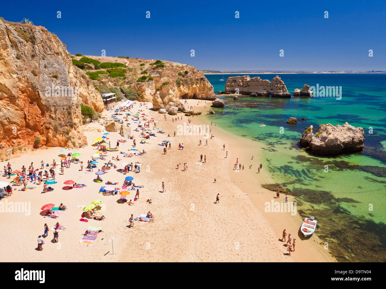 Travel Holidaymakers sunbathing on Praia da Dona Ana sandy beach near the resort of Lagos Algarve Portugal EU Europe - Stock Image