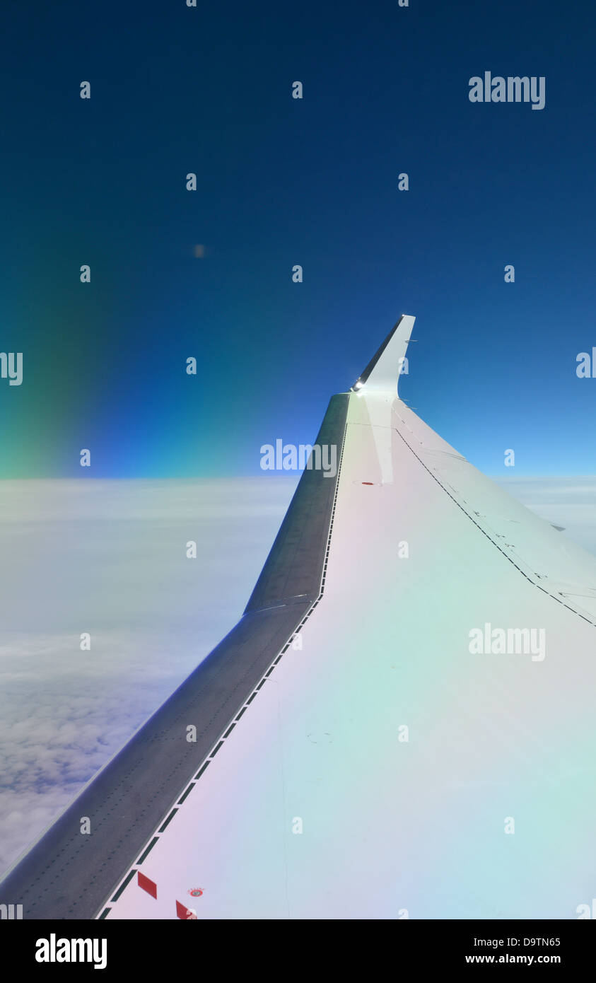 Deep blue sky behind the wing of a jet plane at 44,000 feet, high altitude above the cloud. Blended winglet is visible - Stock Image