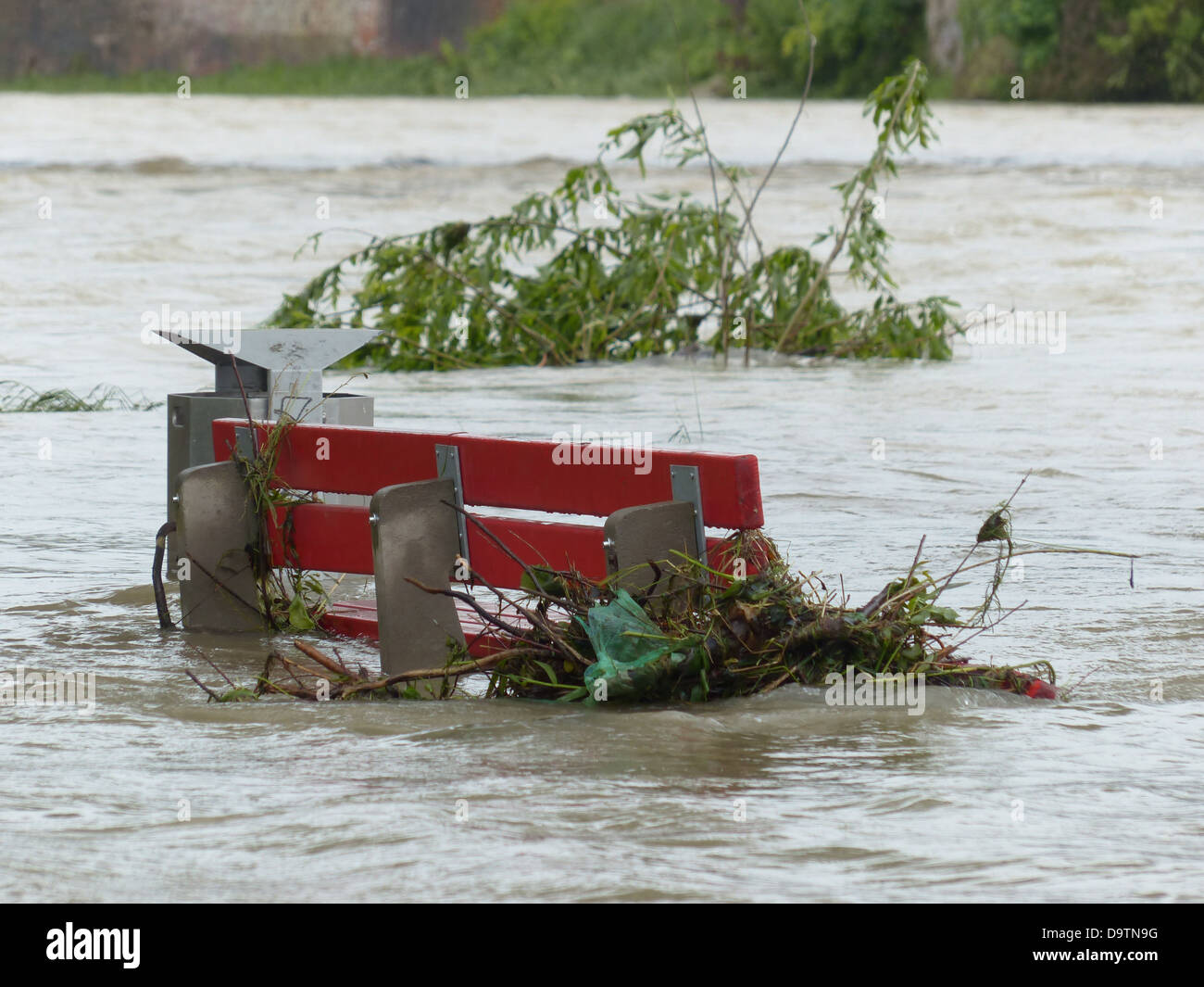 high water park bench flooded red natural disaster Stock Photo