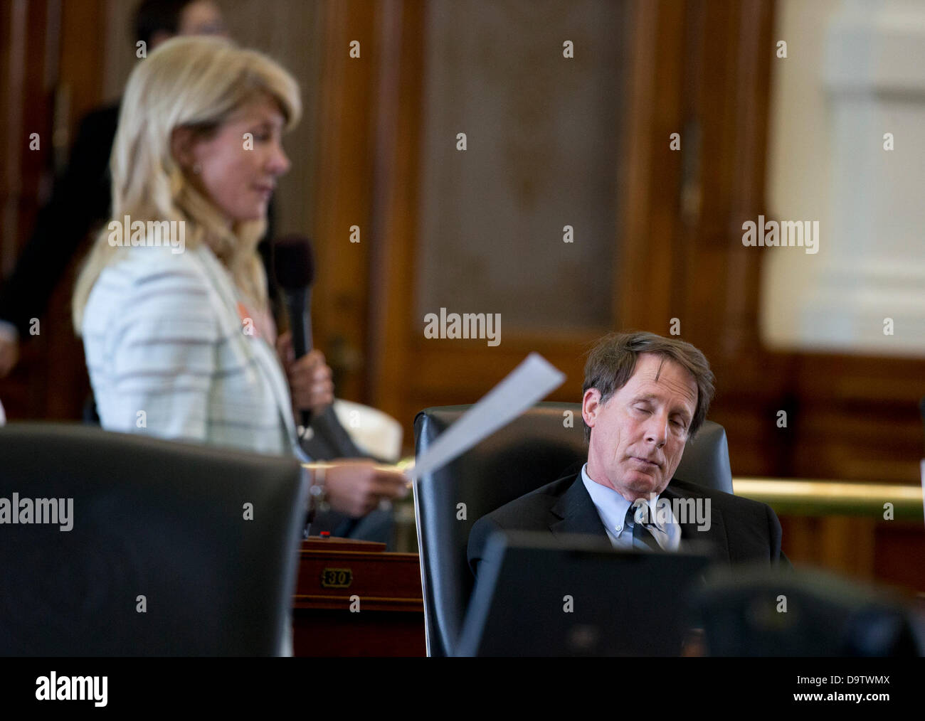 Texas state Sen. Robert Duncan snoozes as Sen. Wendy Davis continues her 11-hour filibuster in the Senate chamber - Stock Image