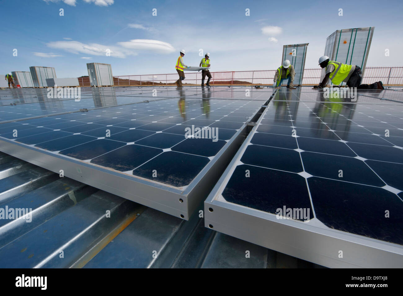 Construction workers install photovoltaic solar electric panels on the roof of the National Renewable Energy Laboratory - Stock Image