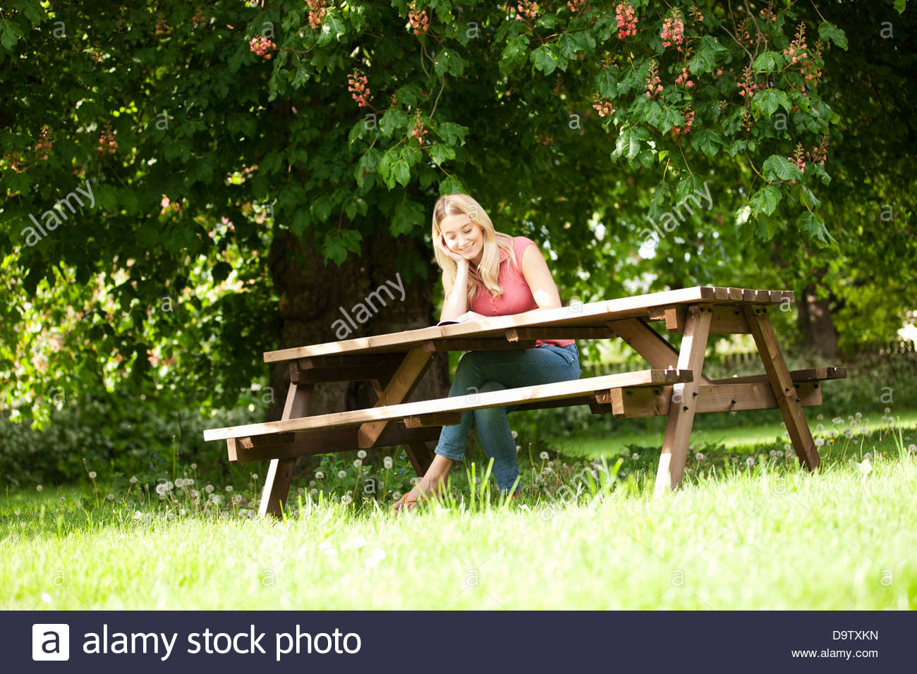 A young woman sitting on a garden bench reading a book, smiling - Stock Image