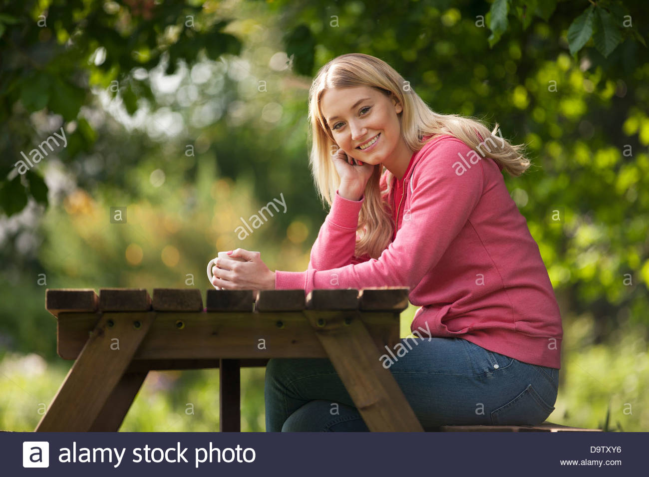 A young woman sitting at a garden bench drinking a hot beverage, smiling to camera - Stock Image