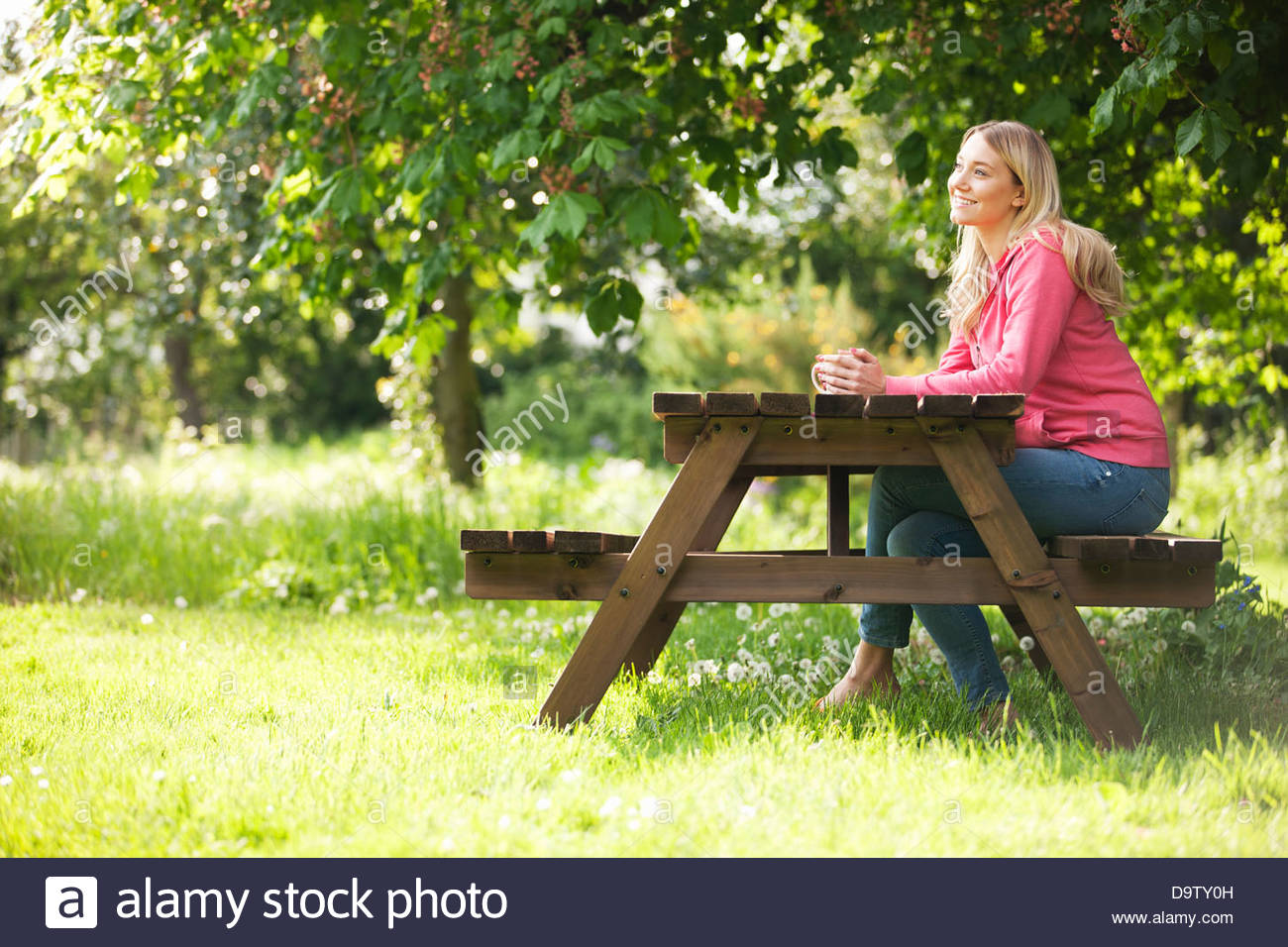 A young woman sitting at a garden bench drinking a hot beverage, smiling - Stock Image