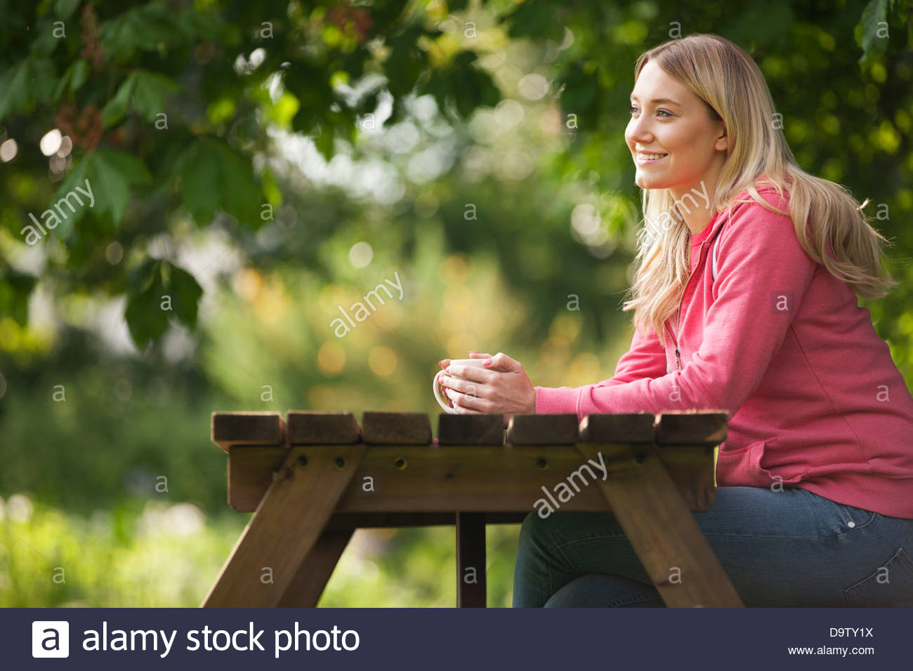 A young woman sitting at a garden bench drinking a hot beverage, close up - Stock Image
