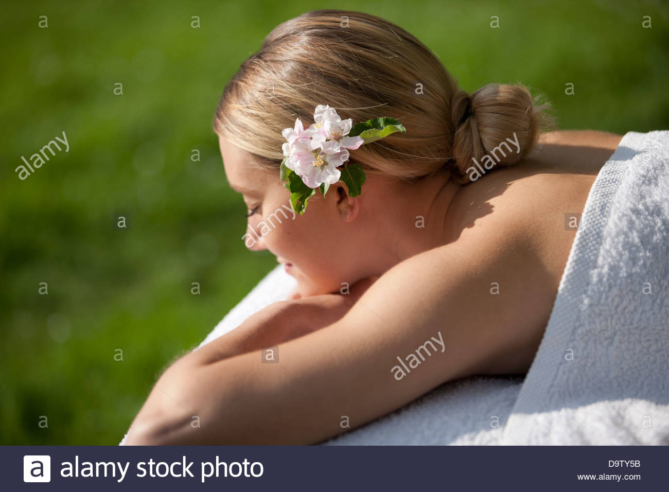 A young woman laying on a massage table with apple blossom in her hair, eyes closed Stock Photo