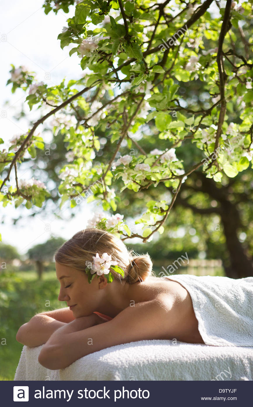 A young woman laying on a massage table under a tree in blossom, eyes closed - Stock Image
