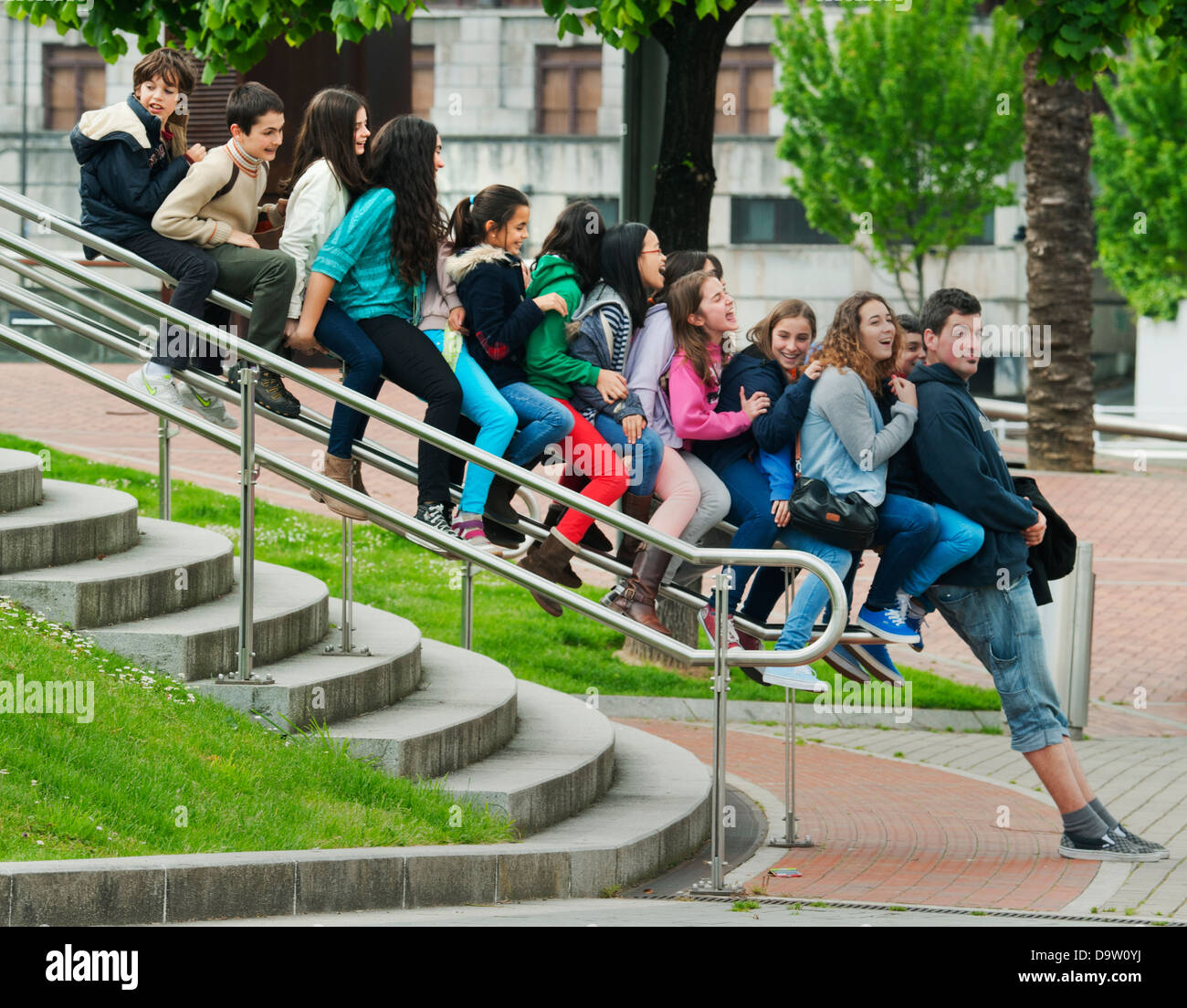 Teacher and students play on bannister, Guggenheim Museum, Bilbao, Spain Stock Photo