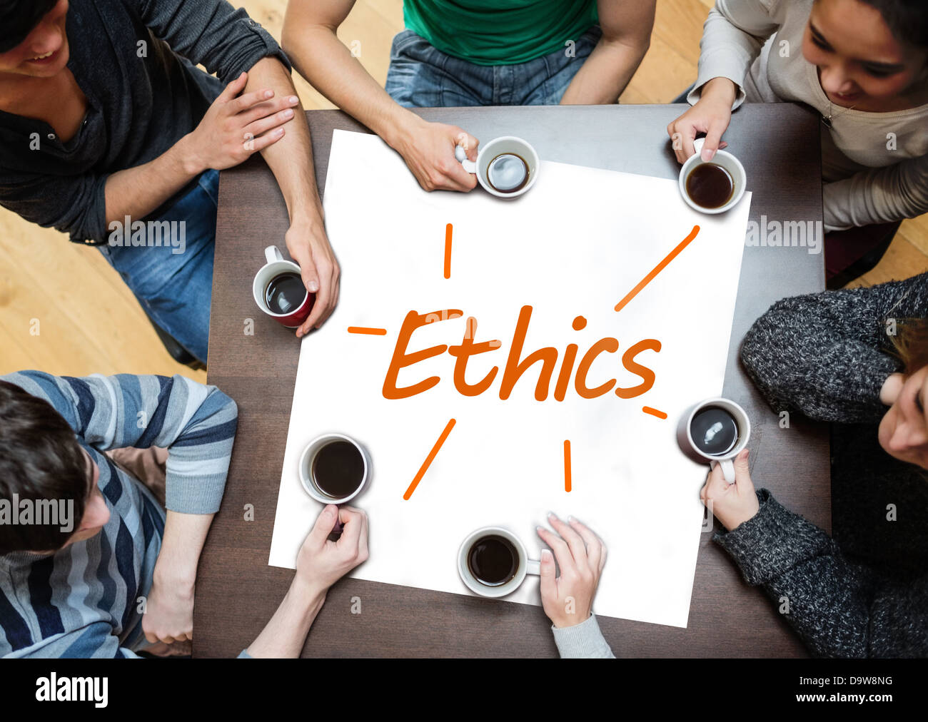 Team brainstorming over a poster with ethics written on it - Stock Image