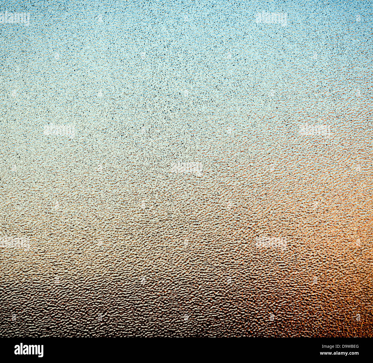 Abstract of stippled glass window pane with ambient colours from outside as background texture - Stock Image