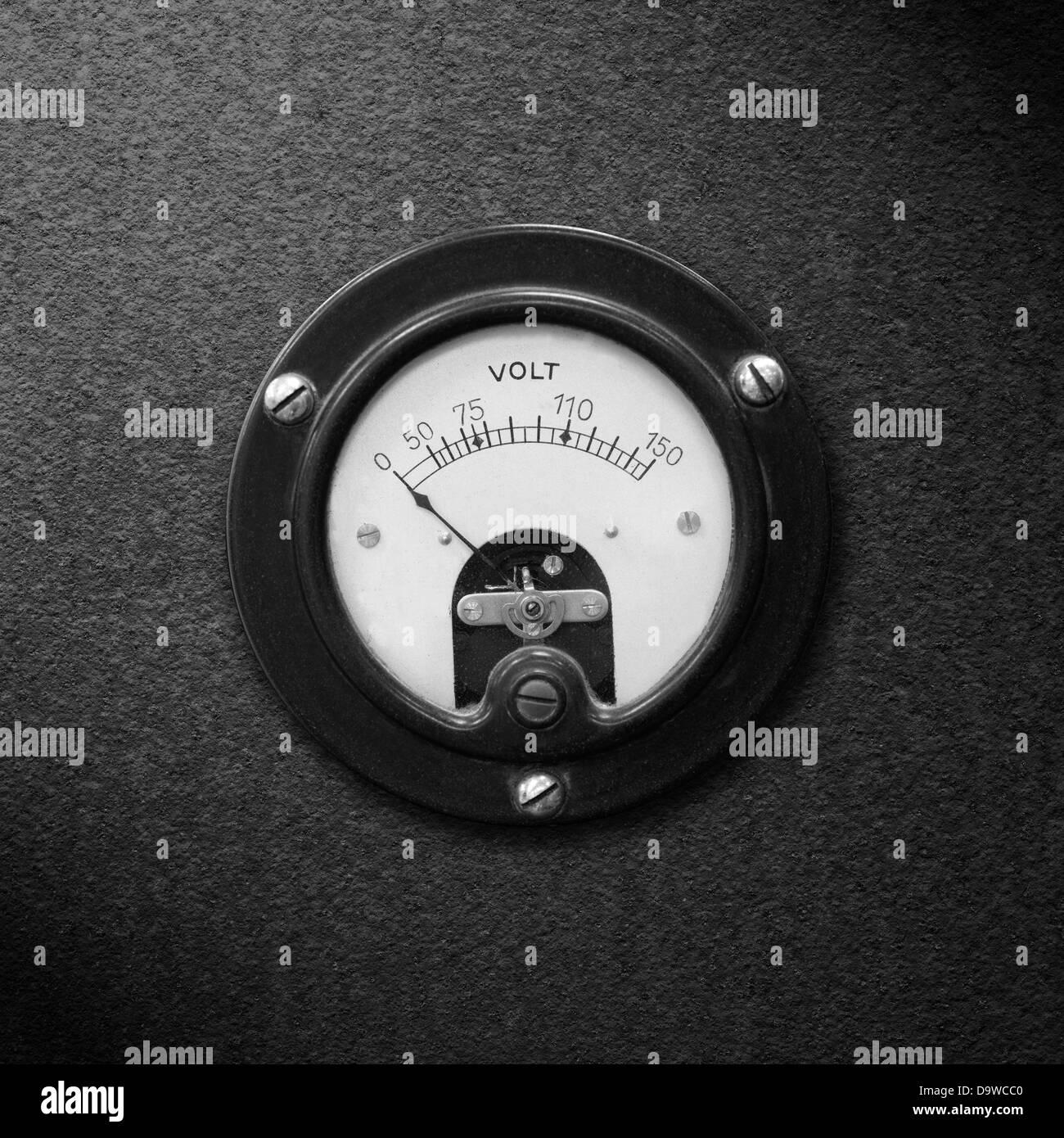 old voltmeter on black metal rough pattern texture or vintage electric measurement - Stock Image