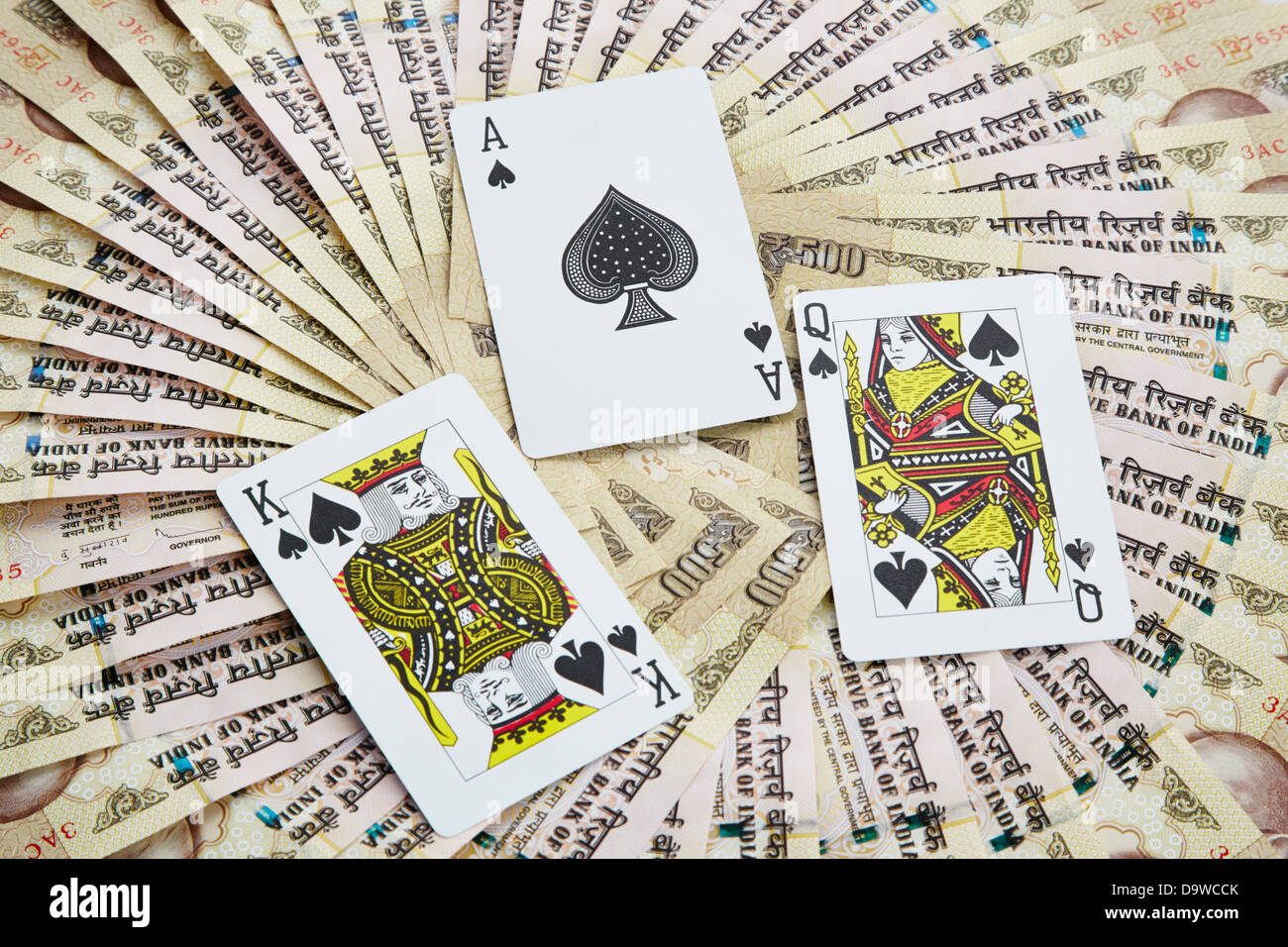 Top view of playing cards surrounded with Indian five hundred rupee notes - Stock Image