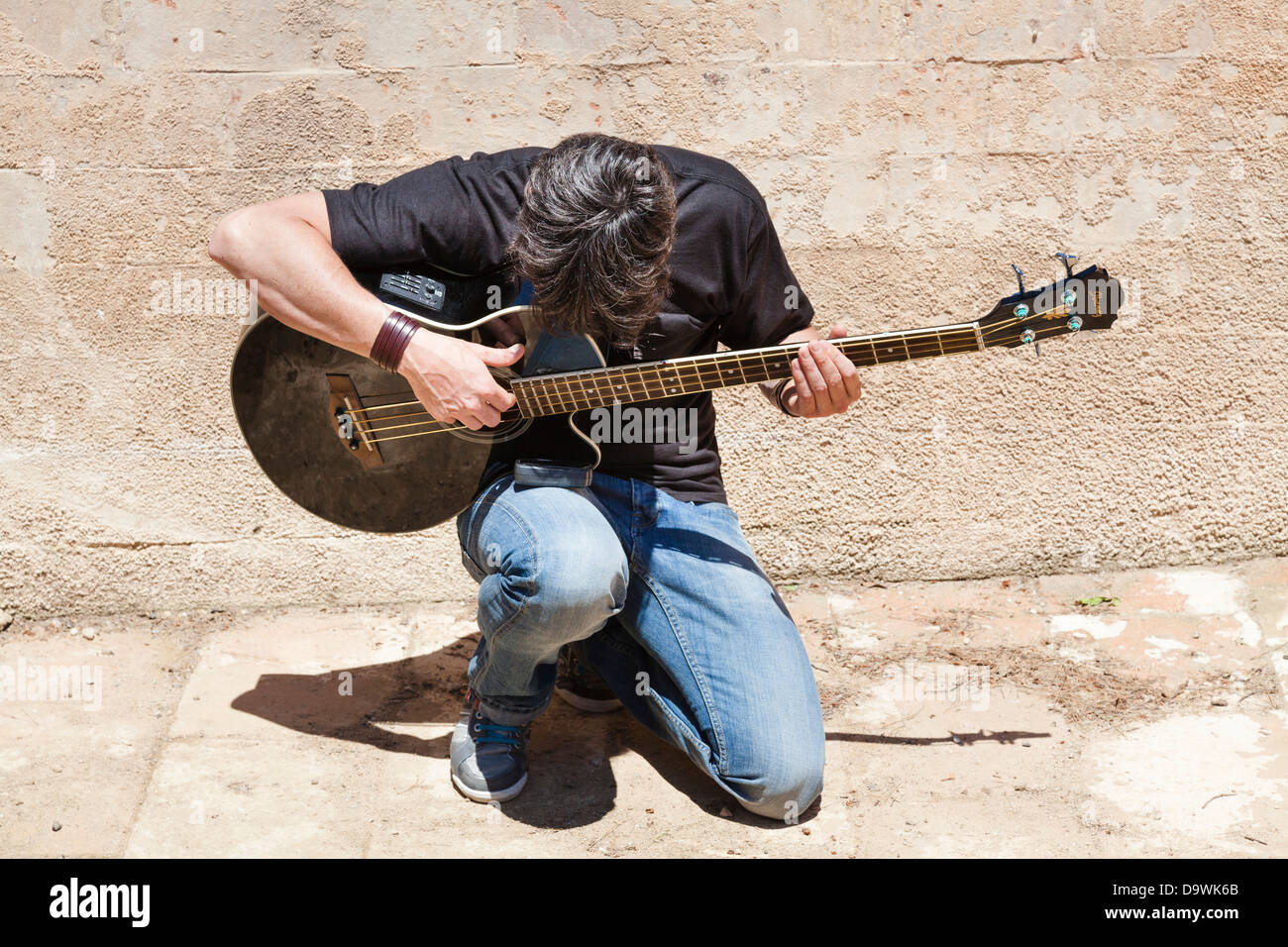 young man playing acoustic guitar kneeling outside - Stock Image