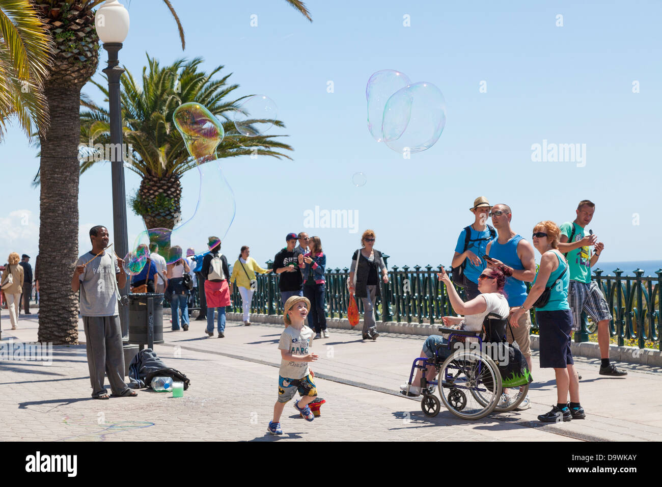 Tourists watching a soap bubble busker at Tarragona. - Stock Image