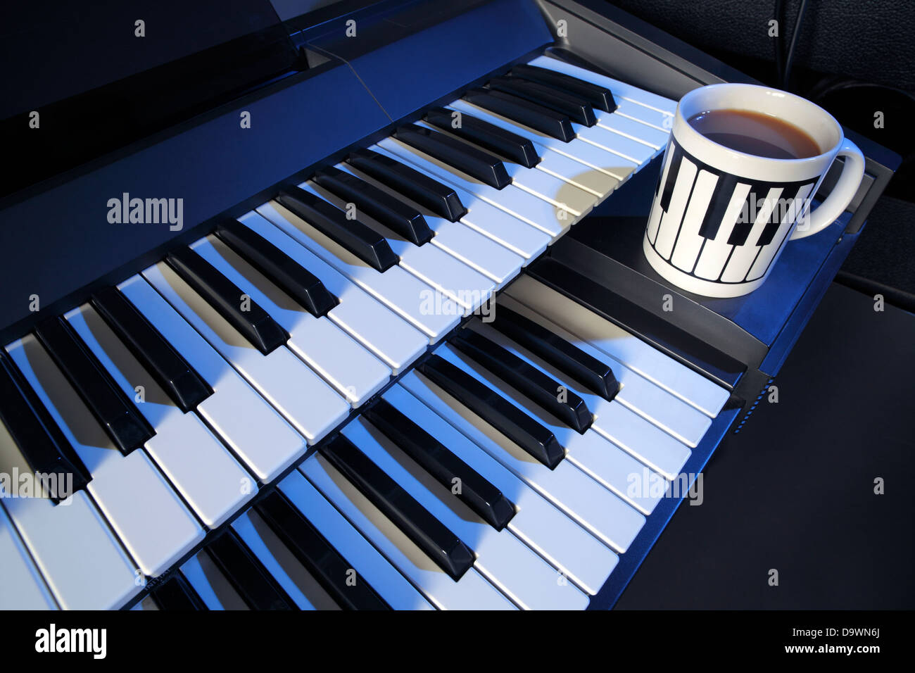 A two manual electric keyboard and a cup of tea (milk, no sugar). - Stock Image