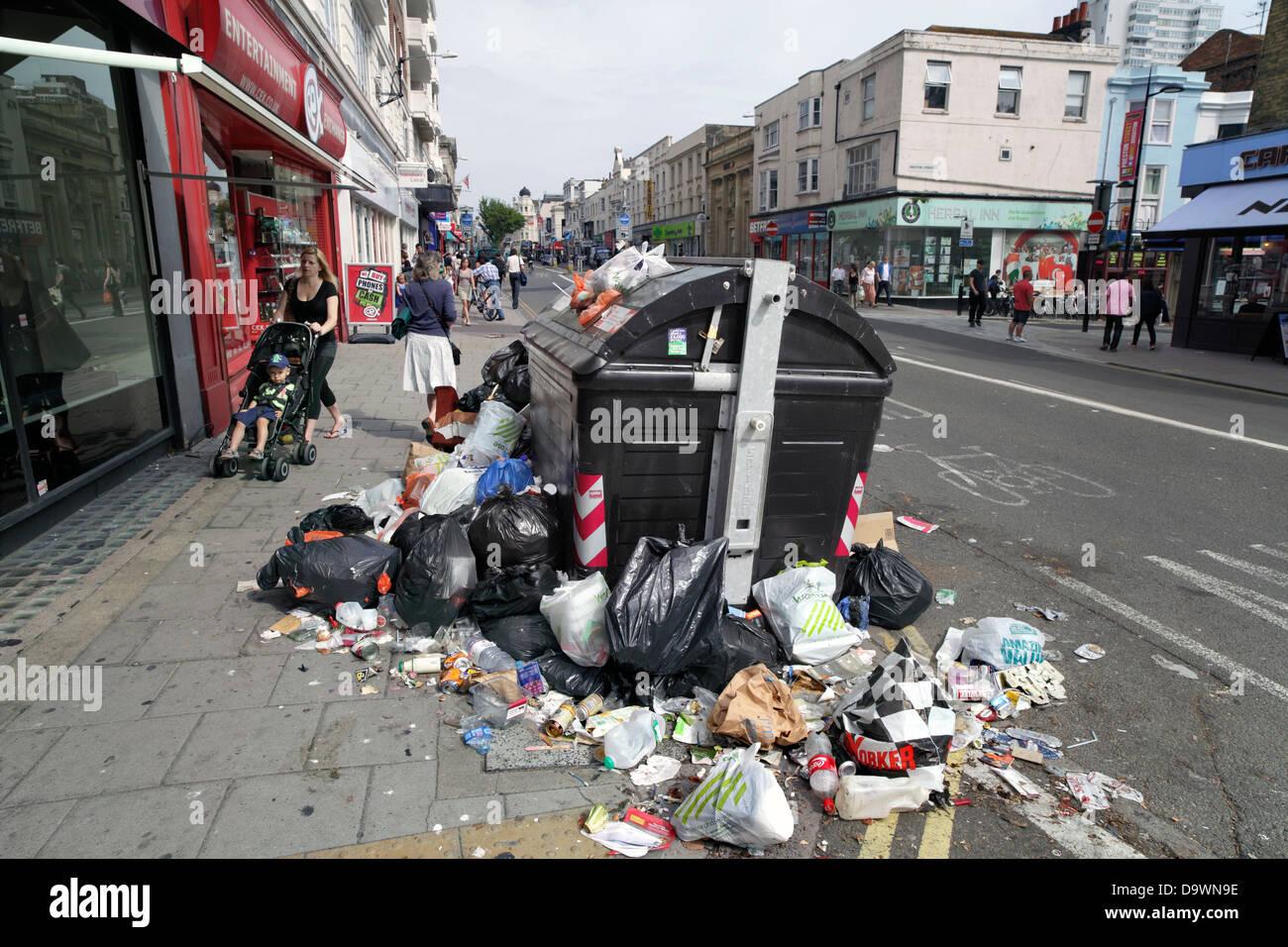 Piles of rubbish around a communal waste bin, Brighton city centre. - Stock Image