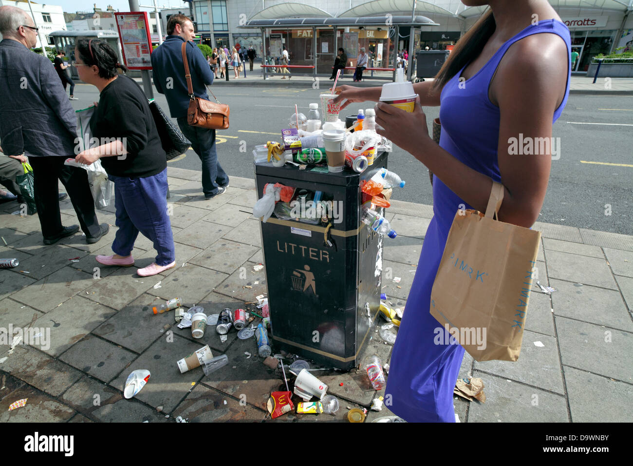 Person placing an empty cup onto an overflowing litter bin. - Stock Image
