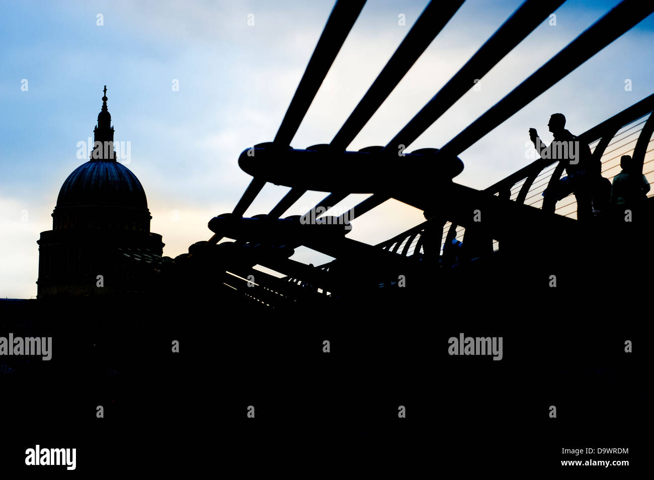 Dramatic back lit view of Saint Paul's Cathedral and the Millennium Bridge over the River Thames, In London, - Stock Image