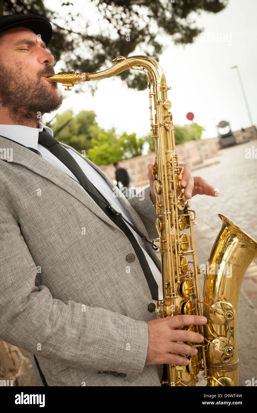 male busker playing saxophone - Stock Image