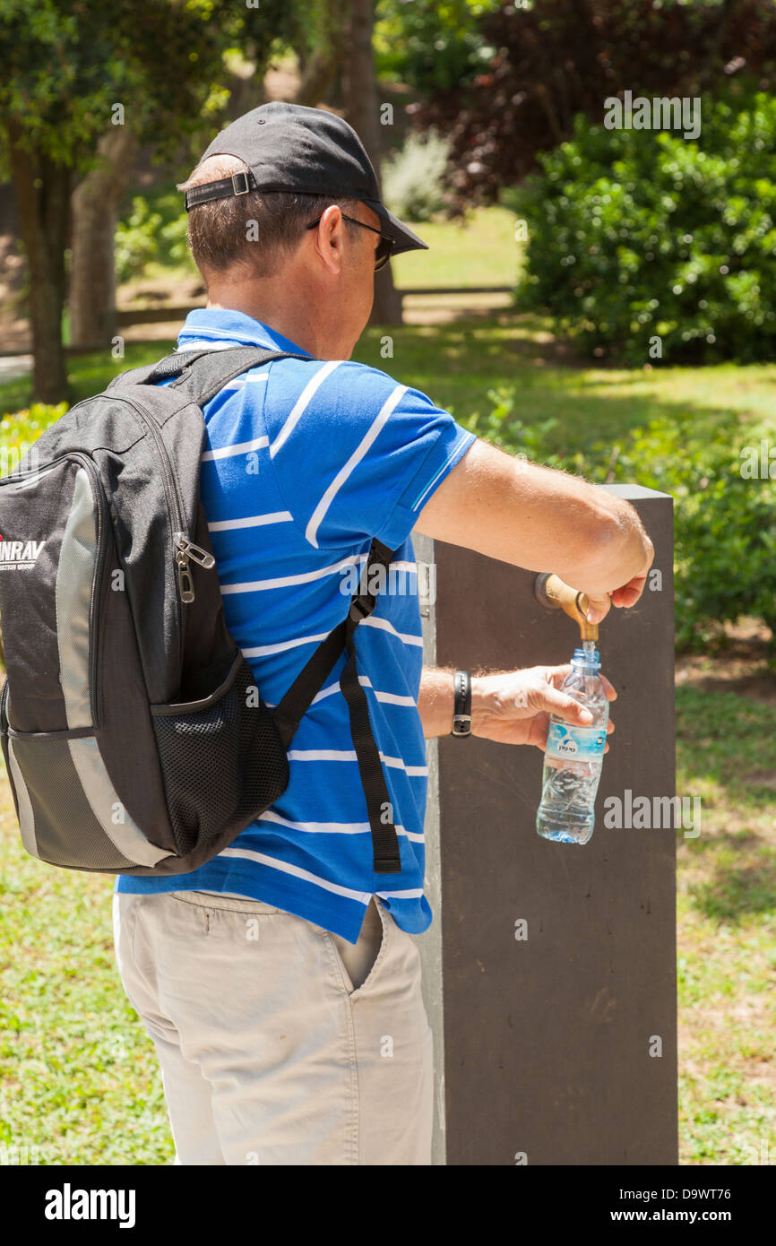 Tourist with backpack filling water bottle from drinking fountain Stock Photo