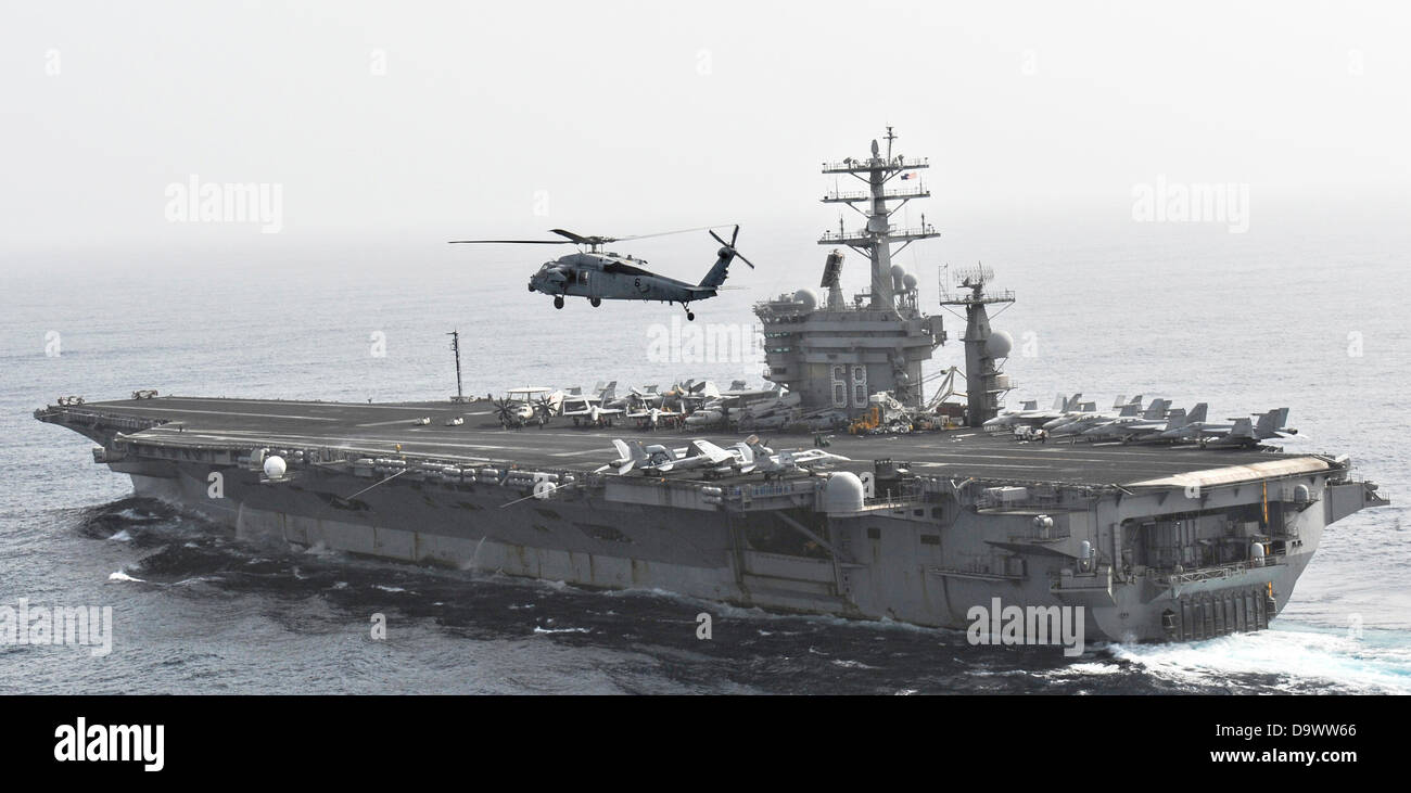 A US Navy MH-60S Sea Hawk helicopter flies by the aircraft carrier USS Nimitz June 26, 2013 operating in the Gulf - Stock Image
