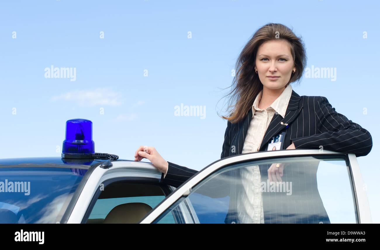 Young female FBI agent standing near car open door - Stock Image