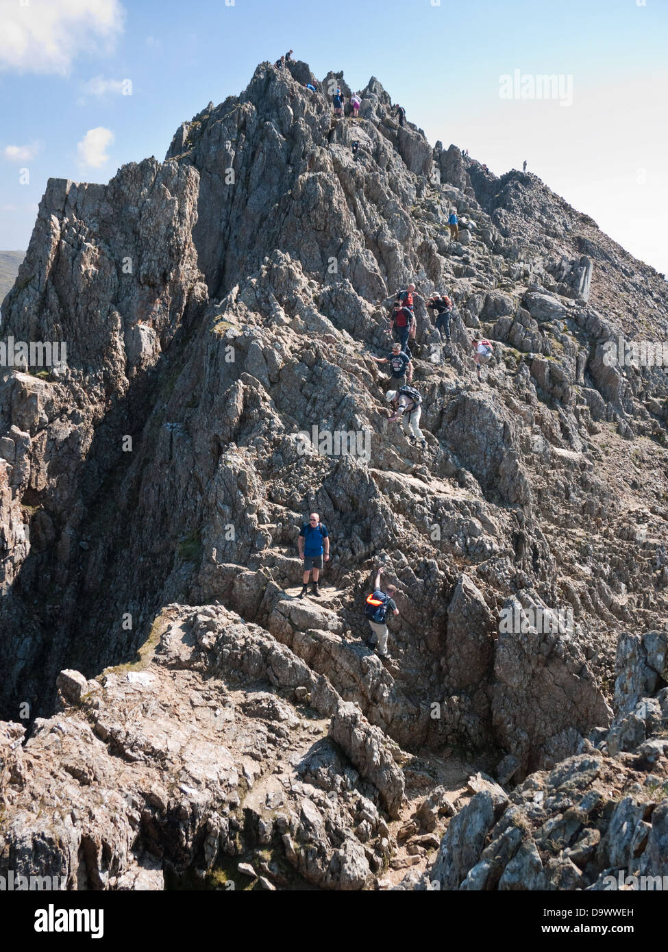 Scramblers descend the pinnacles on Crib Goch, a famous knife-edge arete on the flanks of Snowdon Stock Photo