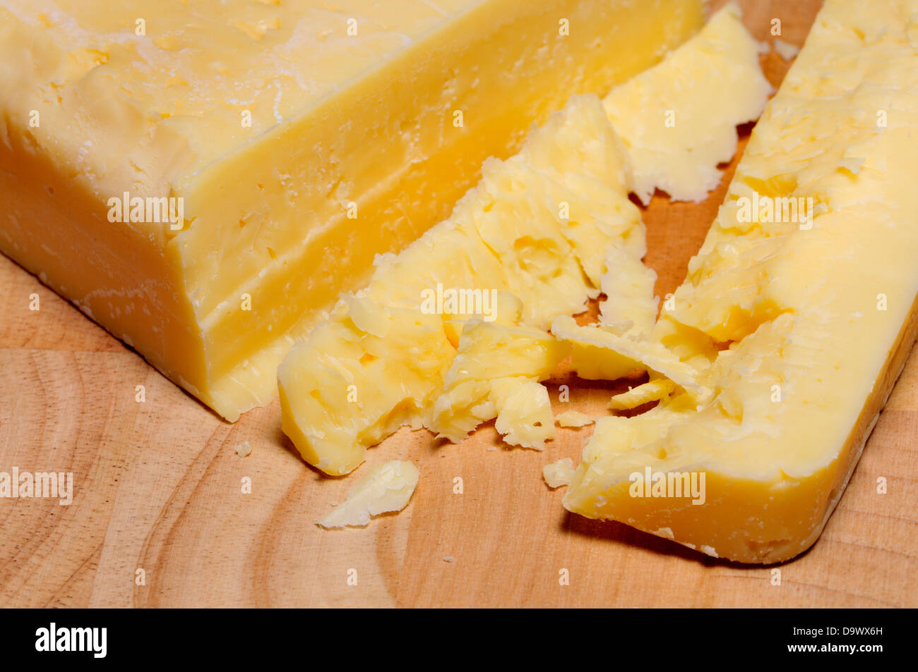 Cheddar cheese on a wooden cheeseboard - Stock Image