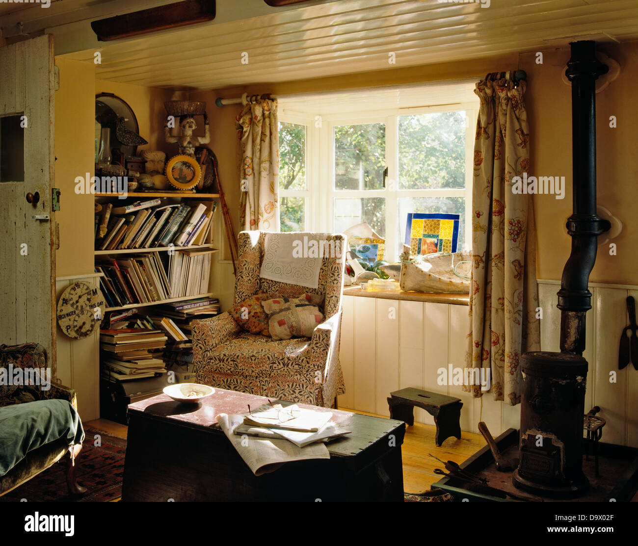 Armchair in front of window in low ceiling cottage living room with ...