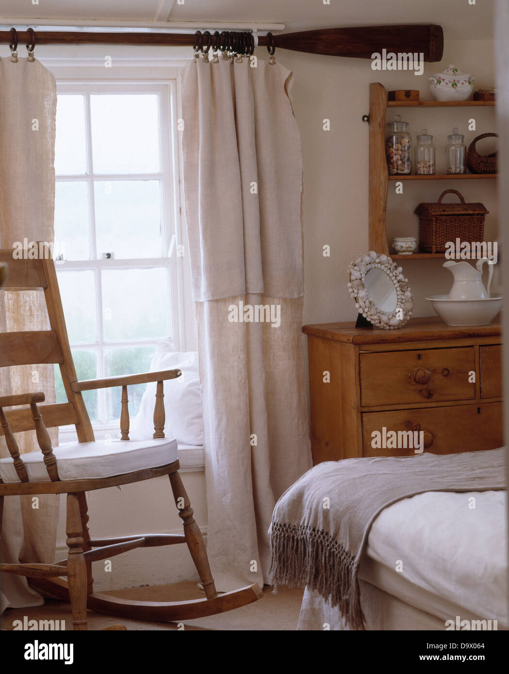 Rocking chair in front of window with old oar used as curtain rod for white linen curtains in white cottage bedroom & Rocking chair in front of window with old oar used as curtain rod ...