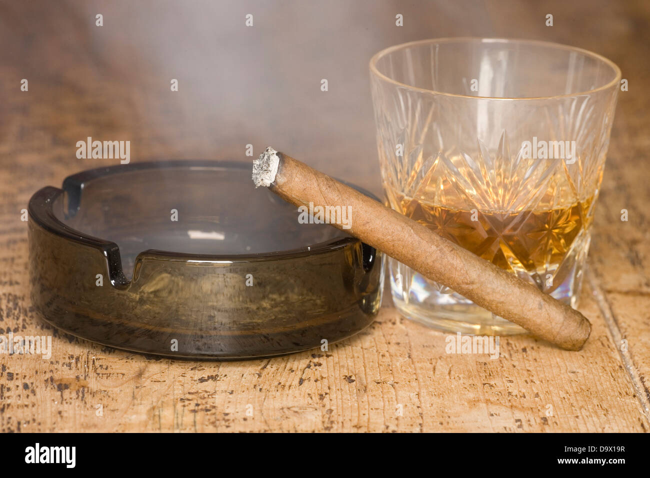 cigar and whisky on a wooden table - Stock Image
