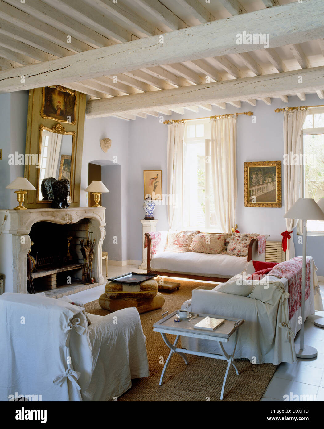 White Loose Covers On Armchair And Sofas In French Country Living Room With  Painted Rustic Beams And Mirror Above Fireplace