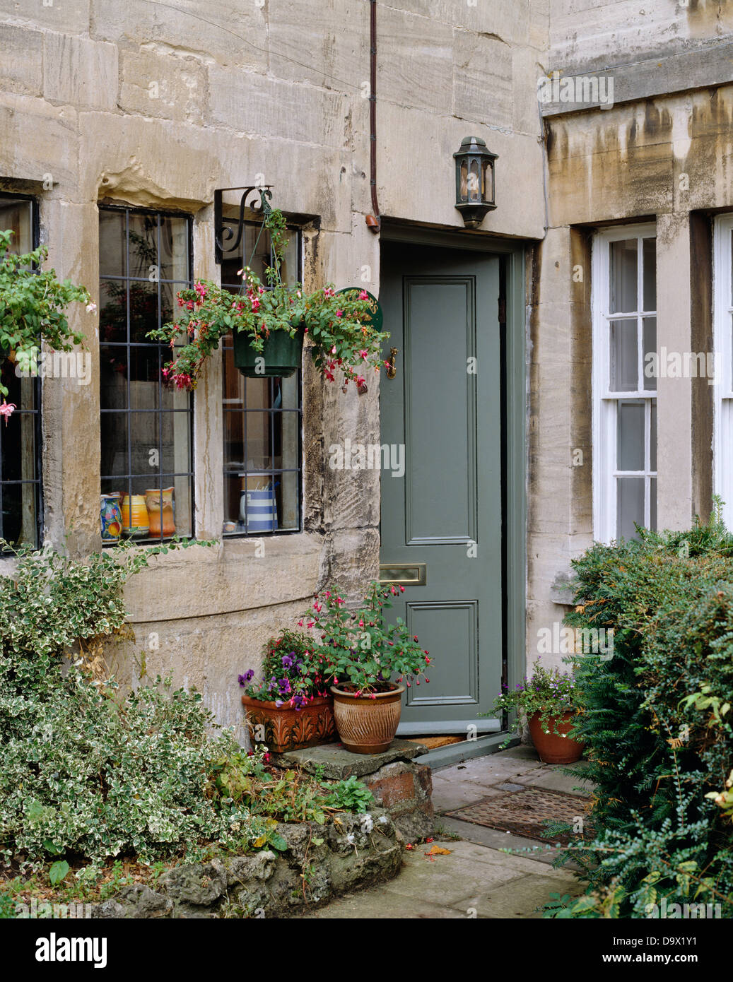 Hanging Baskets Above Window Of Stone Cottage With Gray Painted Open
