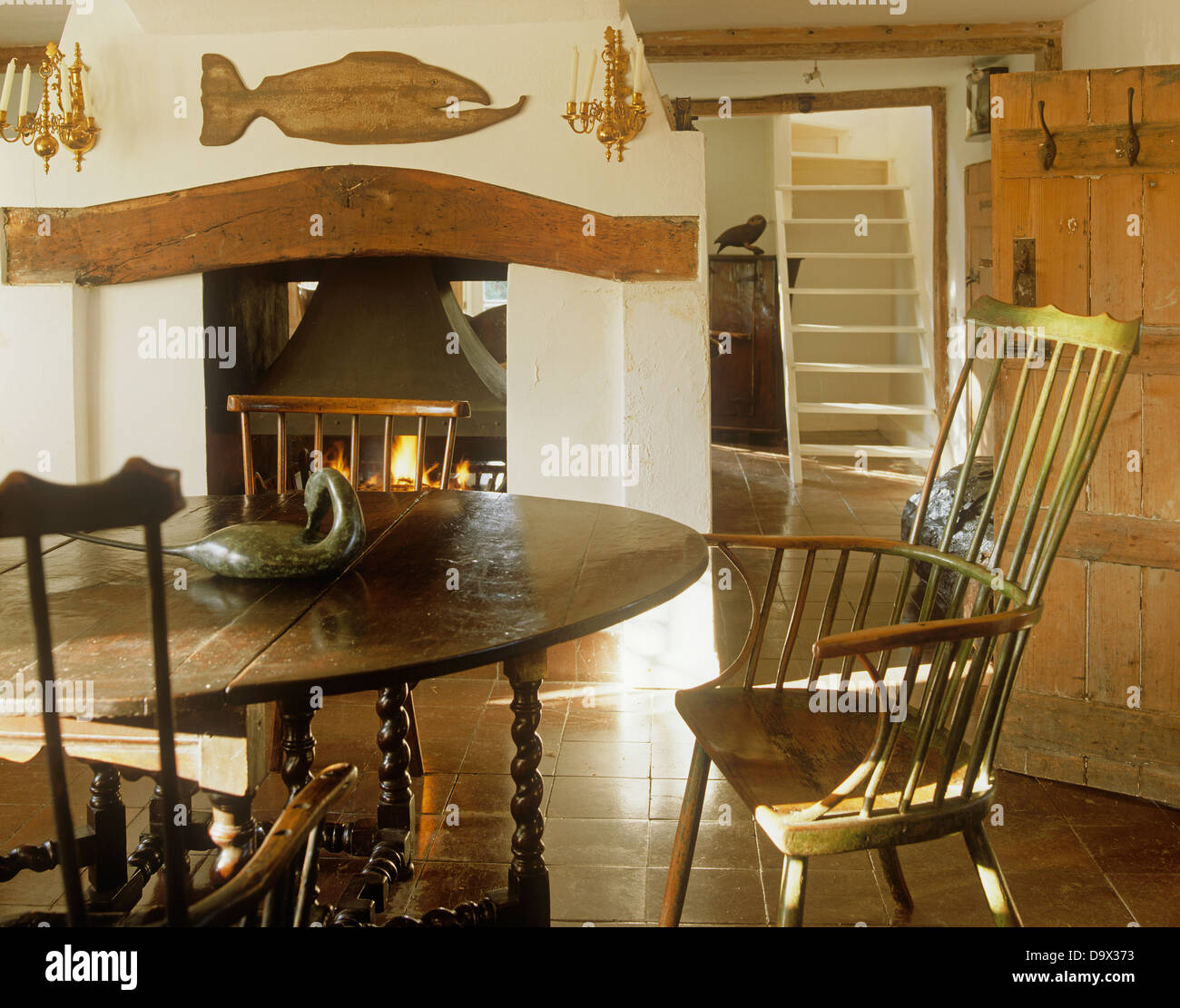 Antique oak table and stick back chairs in country dining room with rustic  wooden fish and beam above fireplace - Antique Oak Table And Stick Back Chairs In Country Dining Room With