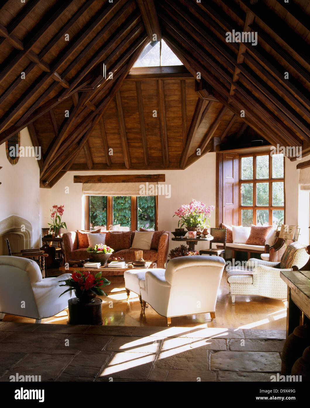 High, vaulted beamed roof in large barn conversion sitting room with white armchairs and sofa and flagstone and - Stock Image