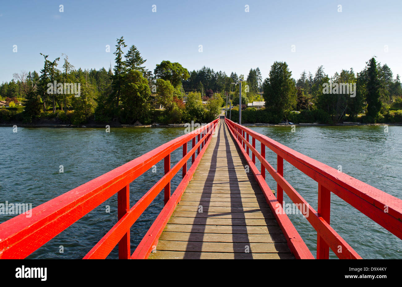 Red painted pier extending back towards the shore.  Fernwood pier, or dock, Salt Spring Island, BC. On the Gulf - Stock Image