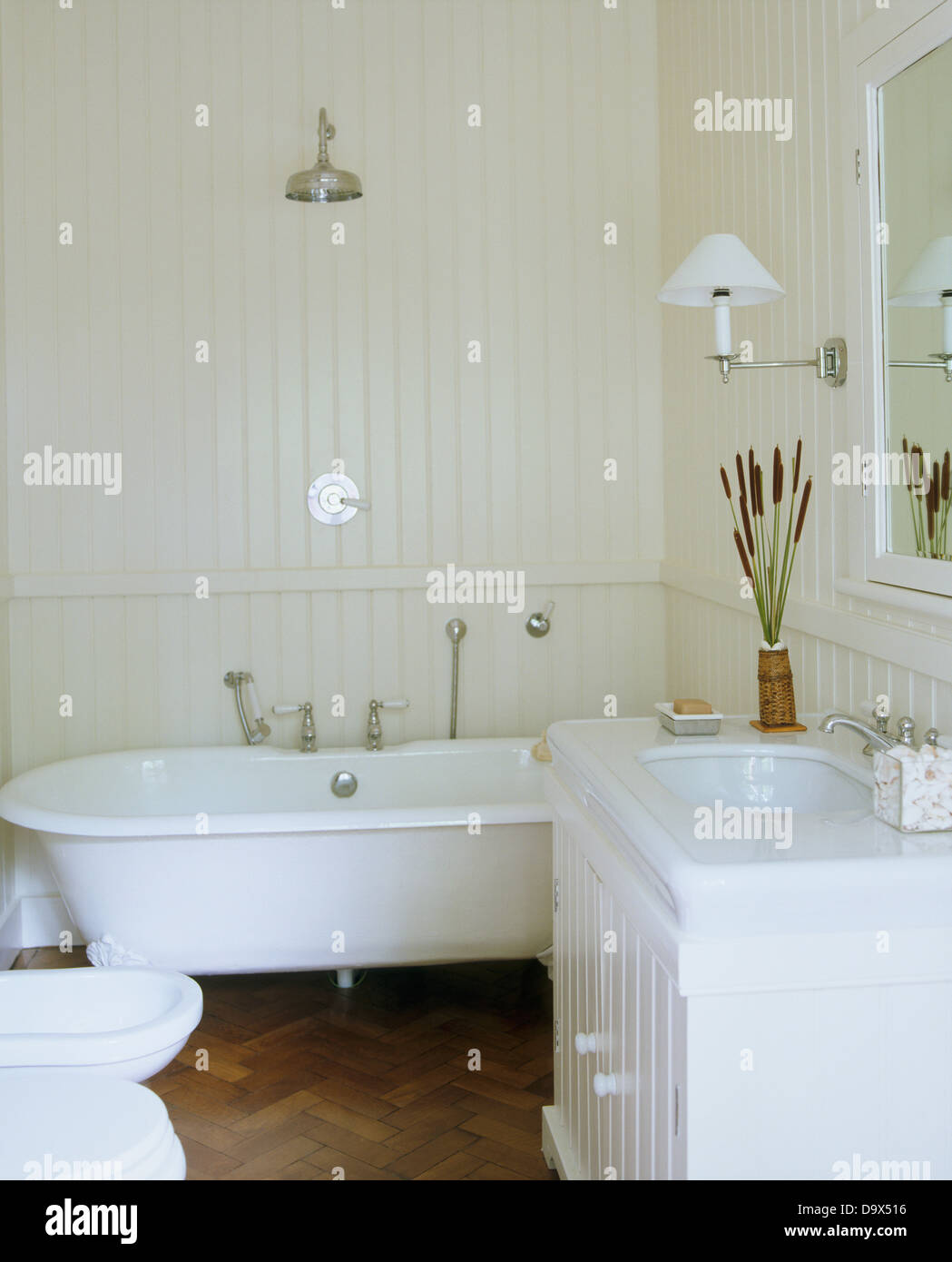 Chrome shower above roll-top bath in white bathroom with white Stock ...
